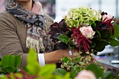 Florist holding summer bouquet of hydrangeas, amaranthus and roses