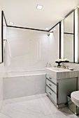 Designer marble bathroom - washstand with marble surround and glass base unit next to bathtub