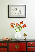 Vase of calla lilies on red and black, Oriental-style sideboard below framed drawing of horse on wall