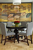 Upholstered chairs at round dining table in front of large-scale artwork with Oriental motifs