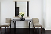 Upholstered chairs next to console table and mirror in classic setting