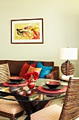 Round glass table with two Oriental place settings and comfortable sofa against wall below modern artwork