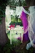 Vintagetisch zwischen großen Baumstämmen im Garten; darauf eine Himbeertorte auf einer Etagere und pinkfarbene Gläser