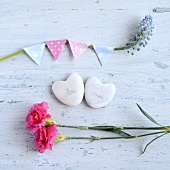 Heart-shaped stones with writing on, between pink dianthus flowers and a decorated stem of grape hyacinths