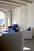 Various armchairs with loose covers and designer standard lamp in Mediterranean interior with sea view