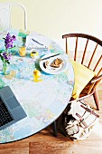Breakfast table jazzed up in youthful style with map of the world applied to table top and vintage chairs