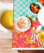Glass table hand-decorated with hippie-style, colourful floral wrapping paper; retro shell chair with yellow seat cushion