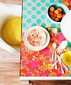 Im Hippie-Look, farbenfroh mit floral gemustertem Geschenkpapier selbst gestalteter Glastisch; Retro Schalenstuhl mit gelbem Kissen