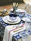 Place setting with blue and white painted bowl next to crystal glasses on white and blue patterned table runner