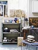 Delicate, blue metal bench in front of vintage shelves with peeling paint against half-height wall and window in workshop-style interior