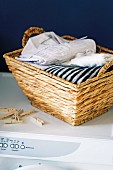 Laundry basket of fresh washing and clothes pegs on top of white washing machine