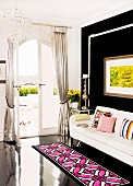 Rug with pink and white geometric pattern on black wooden floor in front of white couch and black wall in corner of living room