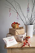 Christmas presents next to reels of ribbon and decorative tags hanging from branches in white, retro china jug