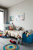 Child's bedroom with toys on rug and blue, cubic pouffe at foot of bed against grey wall