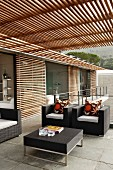 Modern house with elegant, black outdoor furniture on terrace under slatted pergola and with wooden louver blinds on glass wall