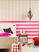 Hot pink horizontal stripes and pastel pink vertical stripes on wall behind rustic bed and chest used as bedside table in girl's bedroom