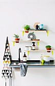 Small shelves mounted freestyle on wall on yellow metal brackets above kitchen sink
