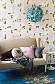 Pillows in various shapes and colors on a light gray couch on blue carpet with a gold pattern in front of a wall with floral pattern wallpaper