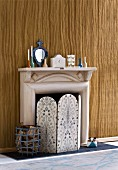 Retro style, fireplace screen with floral pattern and logs in a basket in front of a paper mache fireplace in front of a wall with wood design