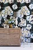 Bouquet of flowers and table lamp on a simple chest of drawers in front of a wall with dark wallpaper with a floral pattern