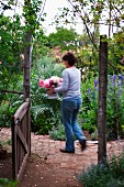 View through open garden gate of woman walking through wild cottage garden holding bouquet