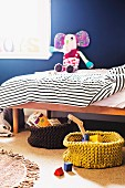 Toys and books in knit baskets in front of a child's bed with stuffed animals