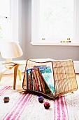 Korbregal auf dem Boden als Aufbewahrung für Bilderbücher; Kinderstuhl im Fiftiesstil und bunte Jonglierbälle