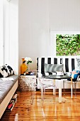 SItting area with black and white striped upholstery and table with post modern, designer kid's chairs