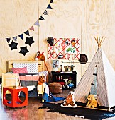 Wooden bed an teepee in a children's room with plywood walls