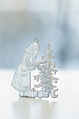 A pewter Christmas figurine: Father Christmas and a Christmas tree