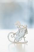 A tin Christmas figurine: a boy on a sleigh