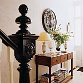 Staircase balustrade with black newel post and spherical finial in front of console table