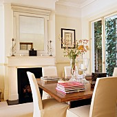 Chairs with pale loose covers and stacked books on wooden table in front of open fireplace in classical living room