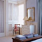 Stacked books on trunk, fitted wardrobes with curtains behind glass door panels and white chest of drawers below mirror on wall in traditional interior