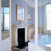 View through open double doors of fireplace with white, carved wooden surround in traditional bathroom with walls painted in pastel shades