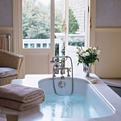 Bathwater in vintage bathtub with vase of white roses on bath surround and view into garden through half-open French doors