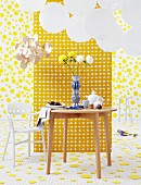 Set wooden table and white plastic chair under round paper lanterns, in front of a room divider with geometric pattern in a room with yellow discs on the floor and wall