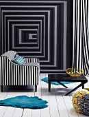 Black and white upholstered armchair and black coffee table on a white wood flooring in front of a wall with optical illusion wallpaper