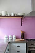 Kitchen counter corner with concrete counter top in front of a violet back splash and white crockery on a wall mounted shelf next to a stainless steel extractor fan