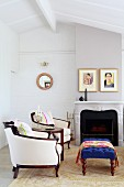 Elegant, white upholstered armchairs and stool upholstered in blue in front of an open fireplace in a no frills room with white wooden beam ceiling