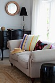 Striped pillows and straw hat on a sofa upholstered in light fabric by a window next to an antique, black commode in the corner of the room