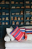 Striped pillows on a sofa upholstered in light fabric in front of a collection of antique books in an open bookcase