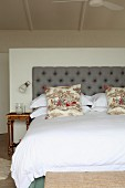 Double bed and vintage pillows in front of a gray upholstered headboard against a half-high room divider in a simple bedroom