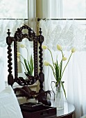 Bouquet of white tulips in glass carafe and antique vanity mirror on table in corner next to window with lace curtain
