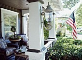 Furnished veranda with stars and stripes flag hanging from column