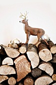 Small plastic stag figurine and silver Christmas tree baubles on stacked firewood