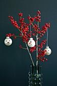 Weihnachtsbaumkugeln mit Schneemanngesicht an Stechpalmenzweigen (Ilex) mit roten Beeren