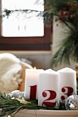 White Advent candles printed with the numbers 1, 2, 3 on plate decorated with fir branches and disco balls