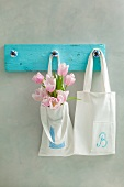 White cotton bags printed with the letters L and B hanging from row of pegs with pink tulips in one bag