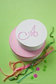 Ribbons, buttons and two decorative pink boxes, one decorated with the letter A